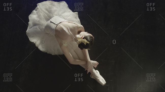 High angle view of performing dancer ballerina in tutu and toe shoes laying gracefully on stage floor