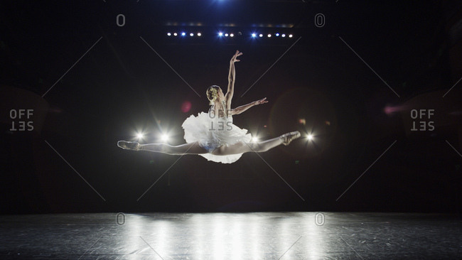 Rear view of serious ballet dancer leaping in costume performing onstage in show