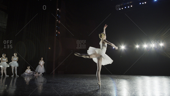 Rear view of serious ballet dancer in costume performing onstage in show