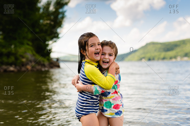 Two young girls hugging each other in lake