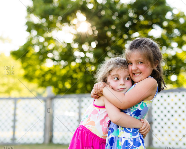 Two young sisters hugging each other in backyard