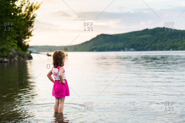 Little girl in pink dress stands in lake at dusk