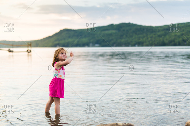 Playful young girl in lake at sunset