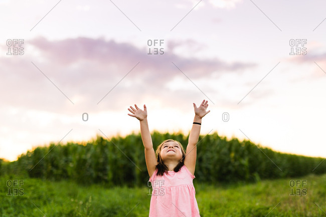 Young girl in field with arms raised at sunset