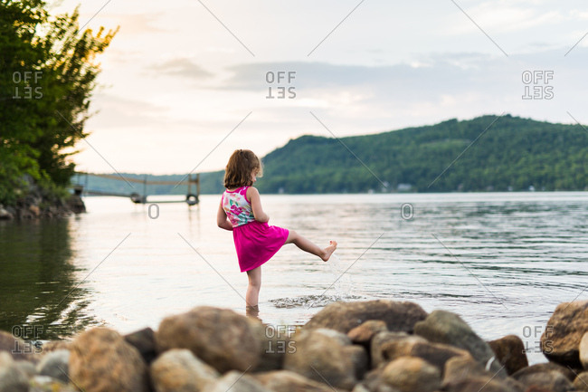 Young girl kicks feet in lake at sunset