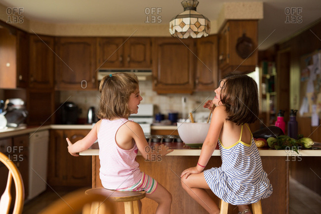 Two young girls laughing at kitchen counter