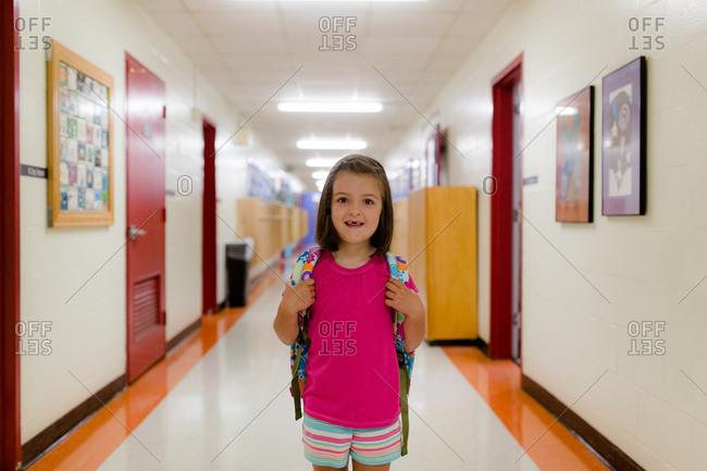 Girl with backpack standing in hallway of school