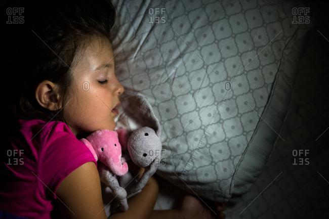 Overhead view of young girl sleeping with stuffed animals