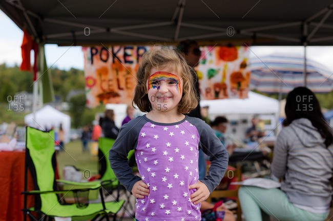 Young girl with rainbow face paint