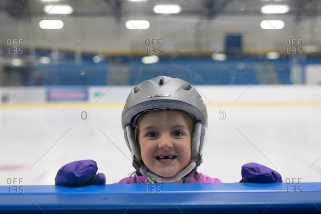 Toothless young girl at window in ice rink