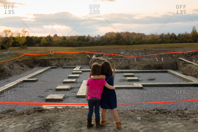 Two young girls standing at construction site