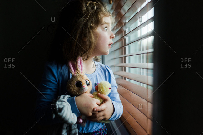 Young girl with stuffed animals looking out window