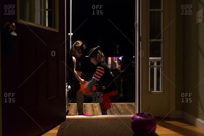 Young girls at front door in Halloween costumes
