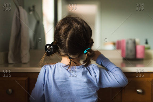 Back view of girl with pigtails brushing her teeth in bathroom