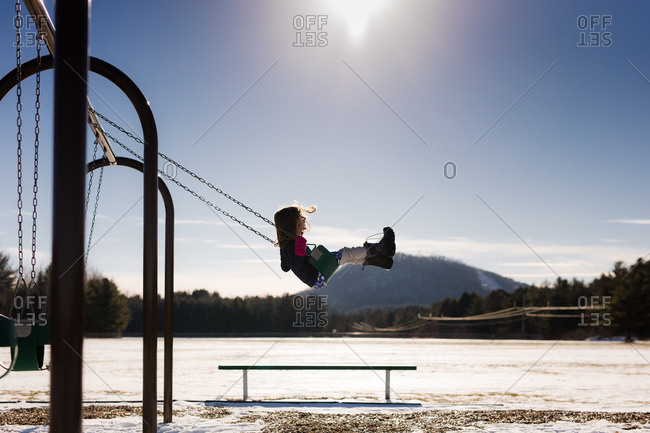 Child on swing at playground in winter