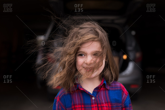 Young girl in plaid shirt with hair blowing in face