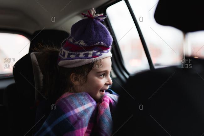 Young girl in ski cap in backseat of car