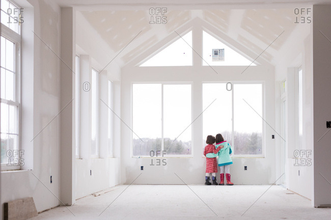 Young girls looking out window of house under construction