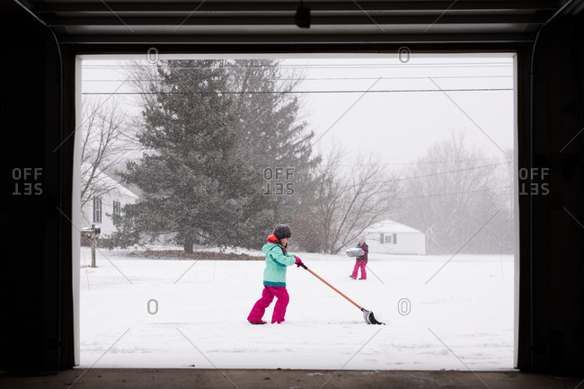 Two young girls shoveling snow