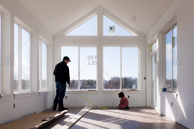 Girl helps father with measuring tape in house under construction