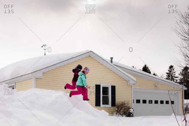Girls jumping off pile of snow into driveway