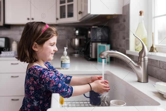 Girl washing hands at kitchen sink