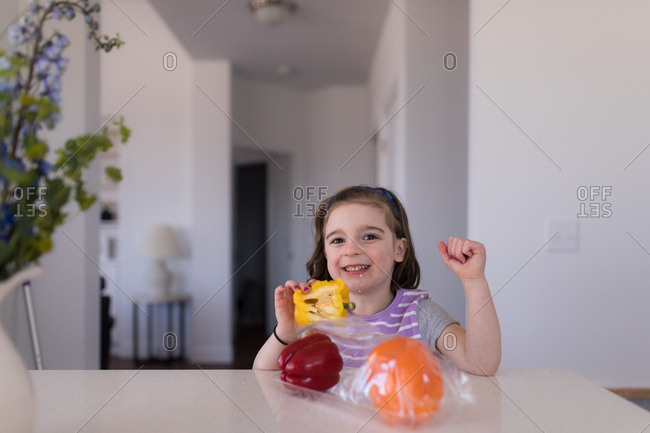 Young girl eating a yellow bell pepper at table