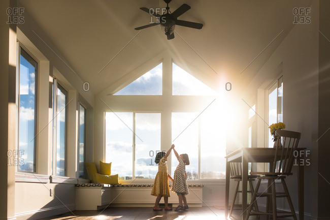 Two girls dancing in sunlit room
