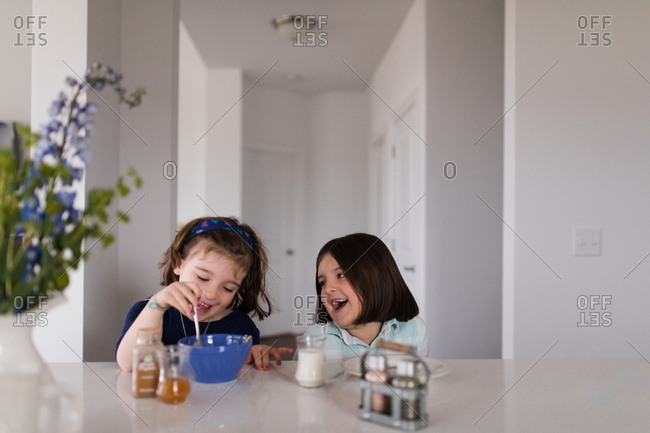 Two young sisters eating at table