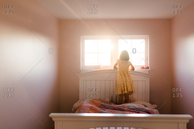 Girl standing on bed to look out window