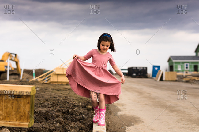 Girl in pink dress balancing on beam at construction site
