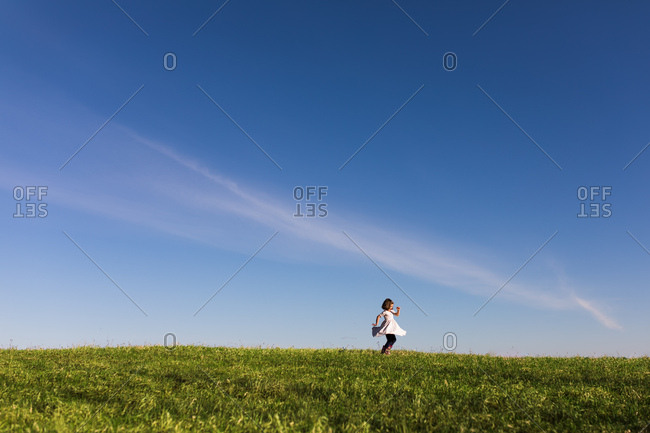 Girl twirling in dress on grassy hill