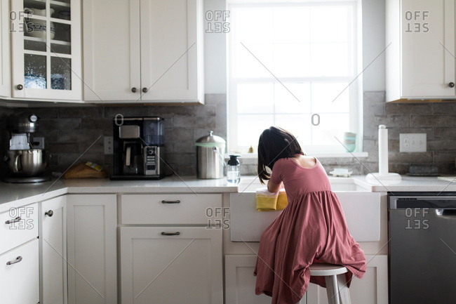 Girl on stool at kitchen sink
