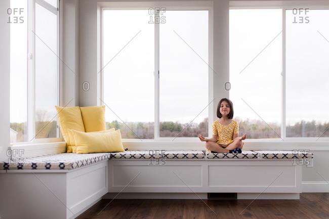 Child practicing meditation on window seat