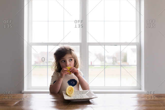 Young girl eating lemon at dining table