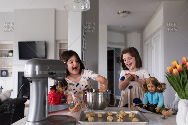 Girls and their dolls making cookies in kitchen