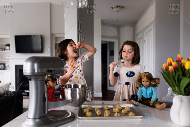 Young girls eating cookie dough in kitchen