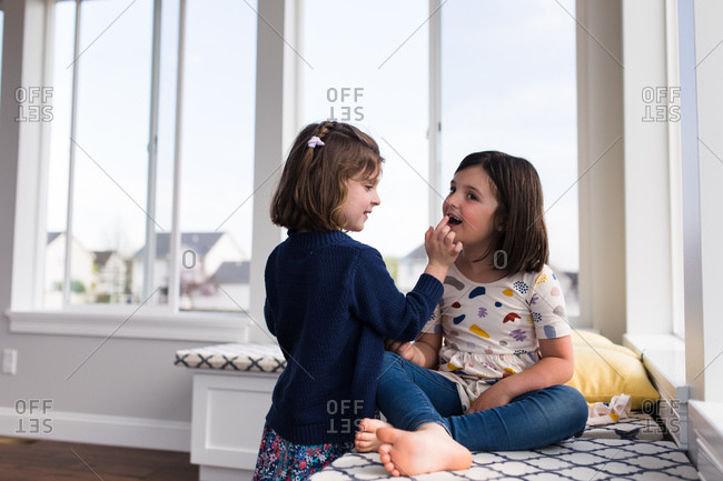 Girl touches her sister's loose tooth