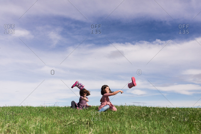 Girls sitting on grassy hill and throwing boots