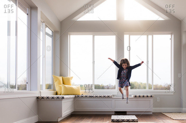 Young girl jumping on cushion in living room