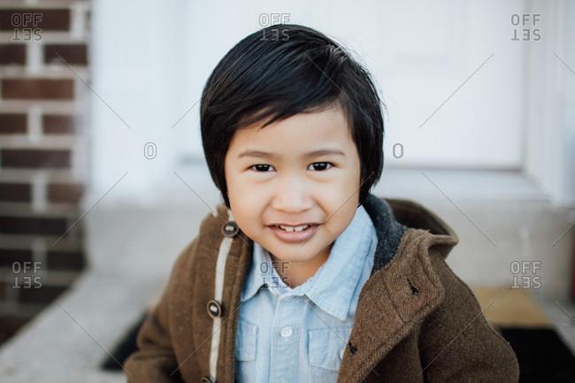 Asian boy in winter coat outside