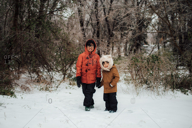 Two boys by woods in winter setting