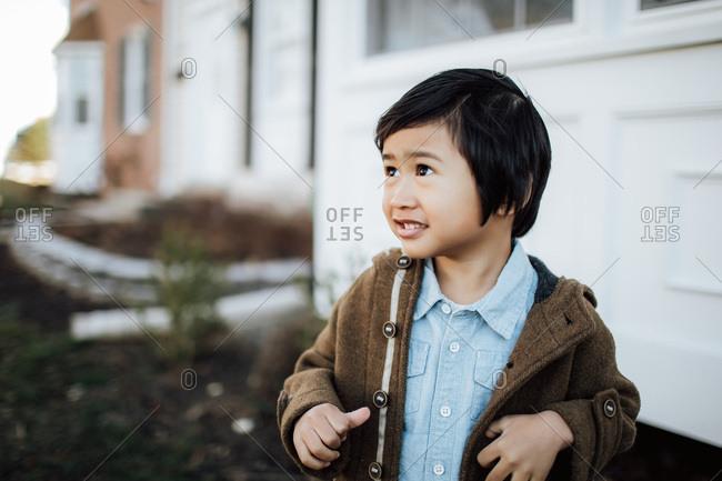 Asian boy in yard wearing coat