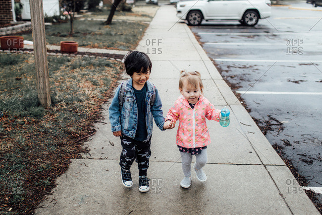 Little boy and girl walking down sidewalk together