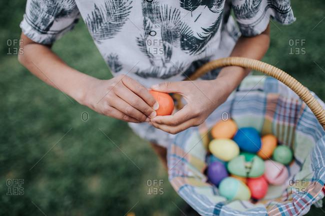Boy opening Easter egg outside
