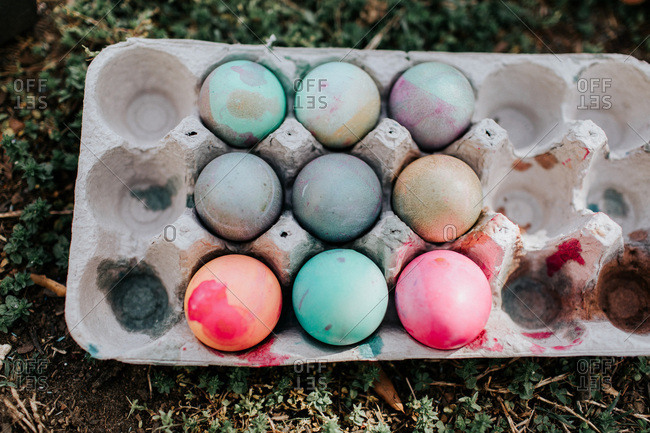 Easter eggs in carton on ground