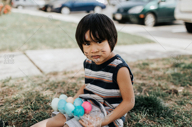 Boy holding carton with dyed eggs