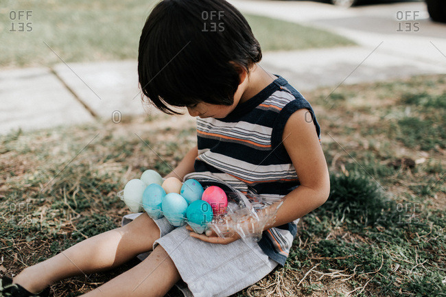 Boy holding carton with Easter eggs
