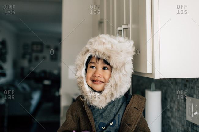 Boy in fuzzy winter hat in home