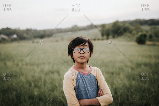 Boy in glasses with arms crossed in field